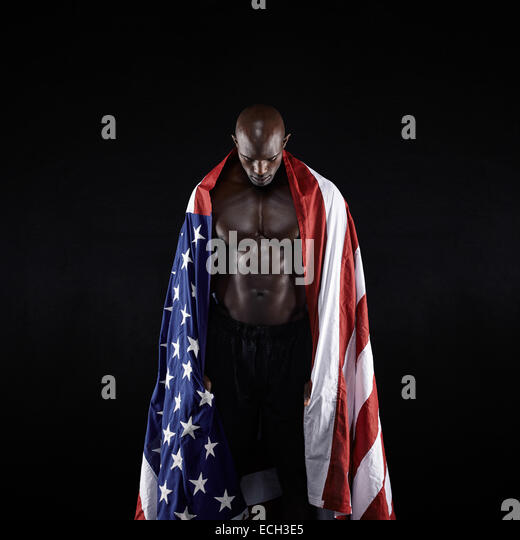 Male athlete carrying an American flag against black background. Studio shot of muscular sportsman with USA flag. - Stock Image