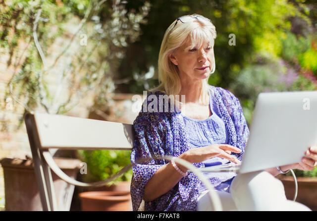 Senior woman using laptop on sunny garden bench - Stock-Bilder