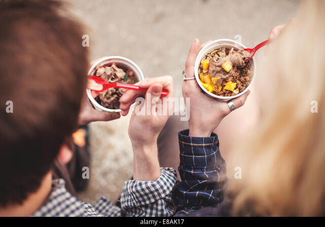 Couple eating tubs of frozen yoghurt treat - Stock Image