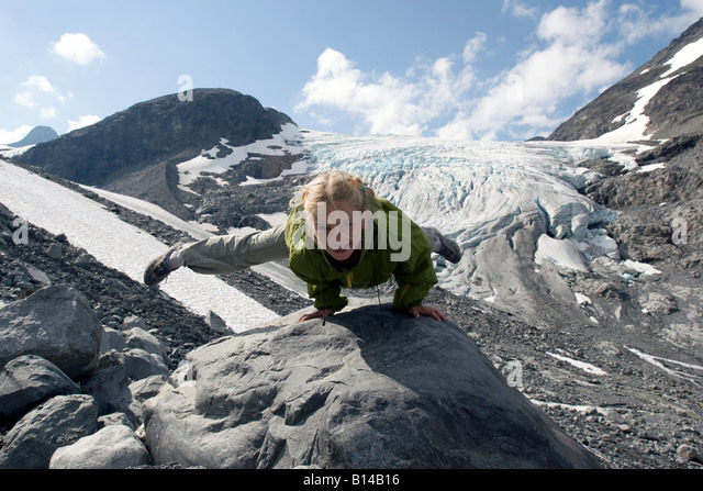 Eight year old blond girl performing acrobatic gymnastics in front of glacier at Jotunheimen in Norway - Stock Image