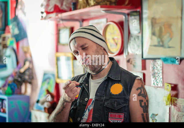 Portrait of male punk shop keeper winking in vintage toy shop - Stock Image