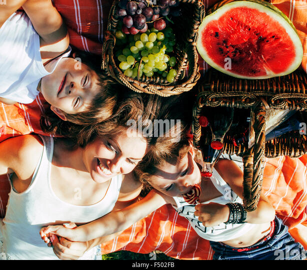 cute happy family on picnic laying on green grass mother and kids, warm summer vacations - Stock-Bilder