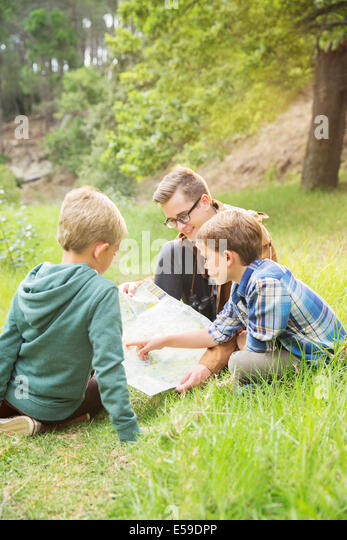 Students and teacher reading map in field - Stock Image