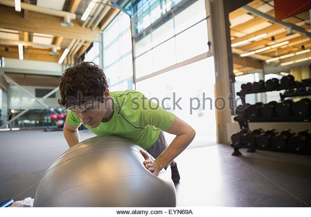 Man doing fitness ball push-ups at gym - Stock Image