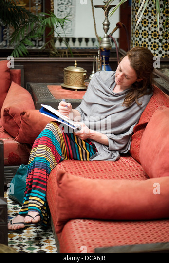 A woman relaxes and writes in her notebook in the elaborate lobby of the riad (small hotel) Dar El Ghalia in Fes - Stock Image