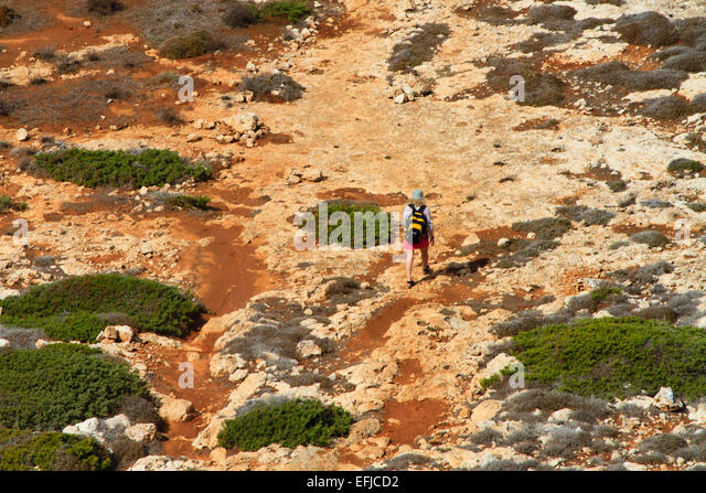 Female backpacker walking across rough ground near Cape Greco, Cyprus. - Stock Image