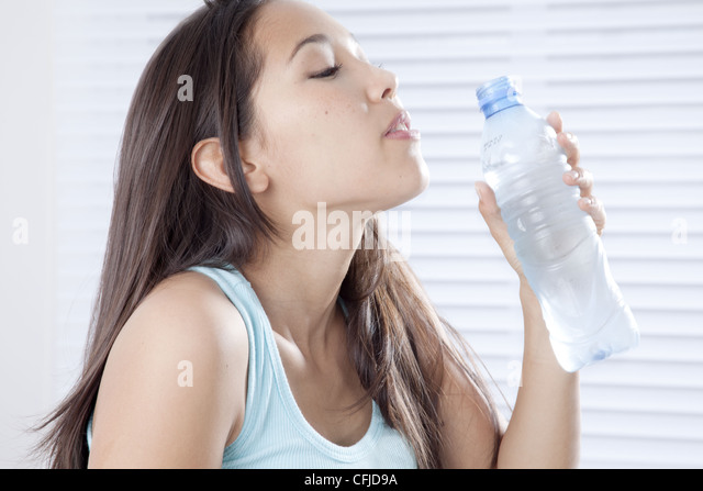 Young woman drinking bottled water - Stock Image