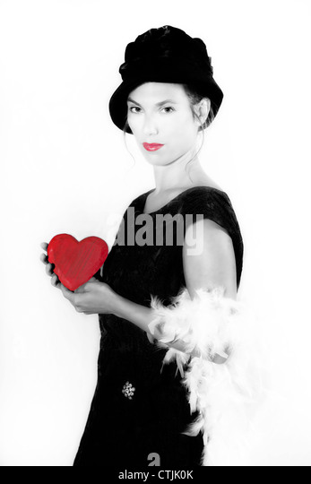 a woman in an elegant black dress holding a red heart - Stock Image