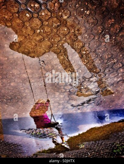 Reflection of children on swings in puddle - Stock Image