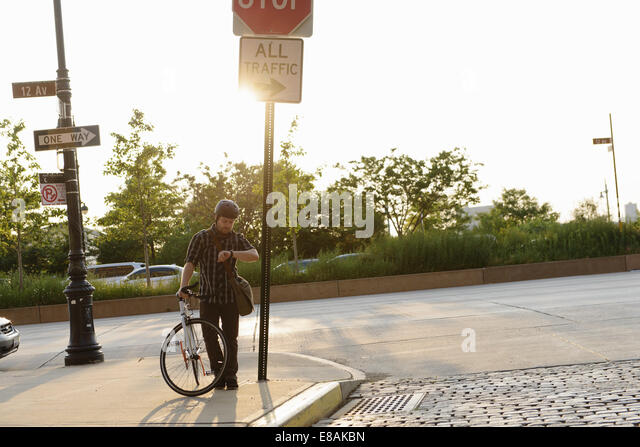 Male cycle messenger checking time on roadside - Stock Image