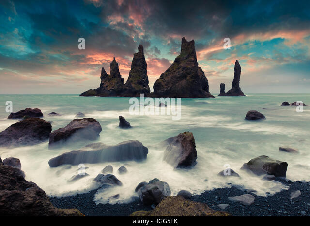 Dramatic seascape of Reynisdrangar cliffs in the Atlantic ocean. Colorful summer sunset in south Iceland, Vic village - Stock Image