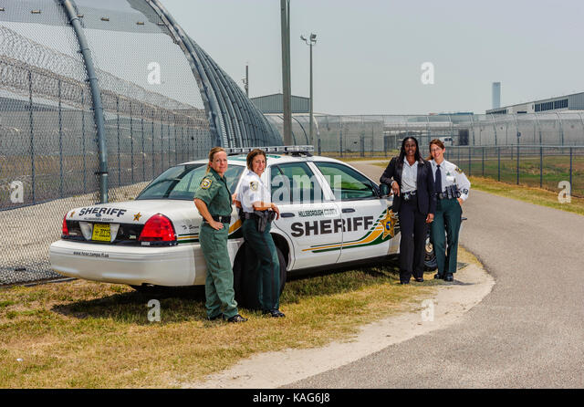 Four female deputies with the Hillsborough County Sheriff's Office standing in front of a patrol car at the - Stock Image