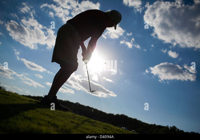 A senior golfer pitches onto a green at a golf practice range. - Stock Image
