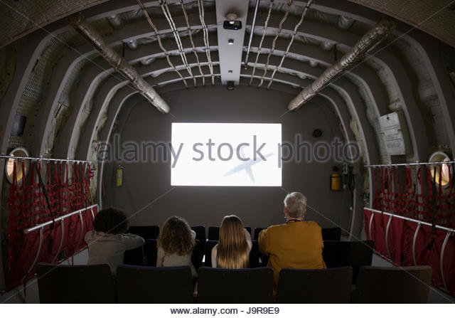 Docent and students watching video inside airplane exhibit on field trip in war museum - Stock-Bilder