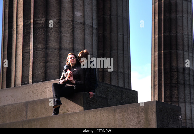 Young Lovers at Calton Hill, Edinburgh , Lothian , Scotland , UK sitting on the neo-classical Greek style monuments - Stock Image