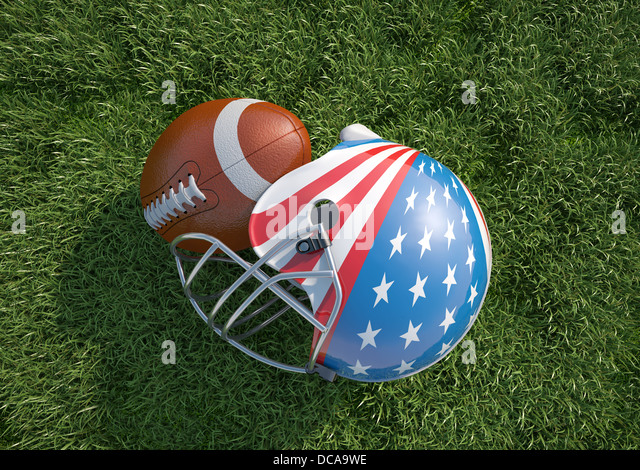 American football helmet, decorated as American stars and stripes flag and oval ball, on the grass. Close up. Top - Stock Image