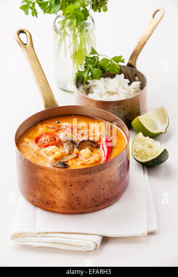 Spicy Thai soup Tom Yam with Rice and Seafood on white background - Stock Image