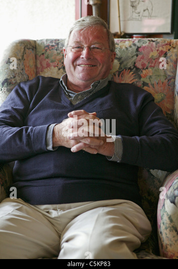 Man (60s) at home, sitting in an armchair and smiling at camera, New Zealand - Stock Image