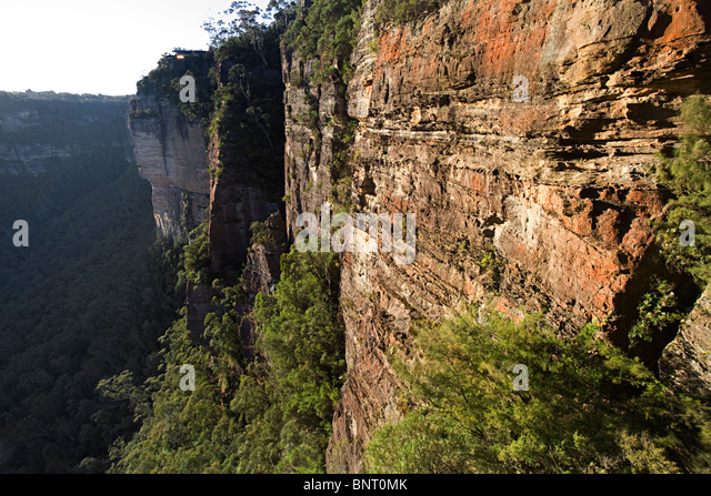 Large orange and grey cliff above jungle. - Stock-Bilder