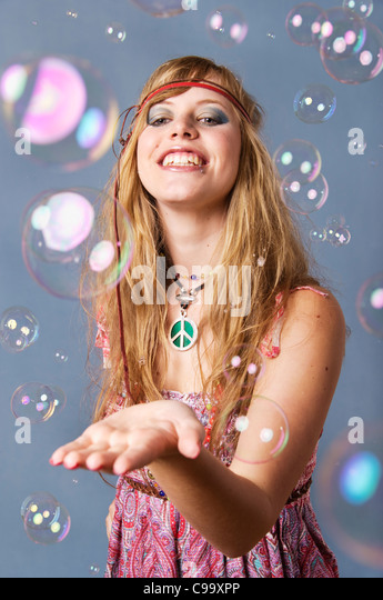 Young hippie woman with bubbles against grey background, smiling - Stock Image