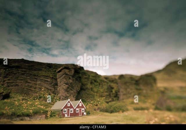 A Red House With A Peaked Roof Beside A Rock Ledge; Iceland - Stock Image
