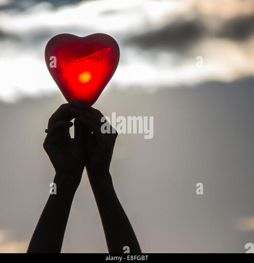Woman's hands holding a heart shape object - Stock Image