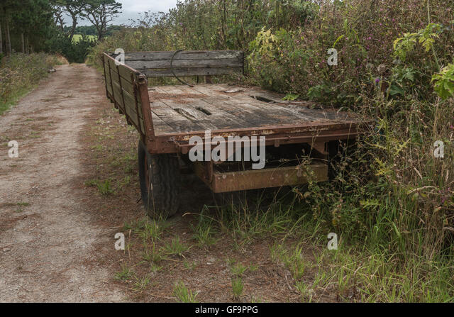 Farm track with aging and rusting farm trailer abandoned to one side. - Stock Image