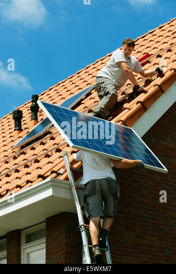 Workers carrying and installing solar panels on roof of new home, Netherlands - Stock Image