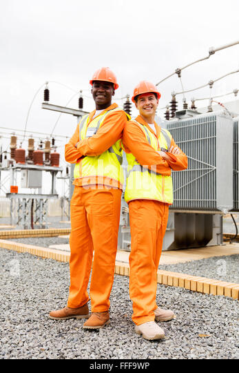 multiracial electrical co-workers in electric substation - Stock Image