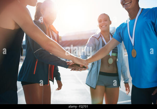 Shot of a group of young sportsmen with medals piling their hands while standing in a huddle. Successful team of - Stock Image