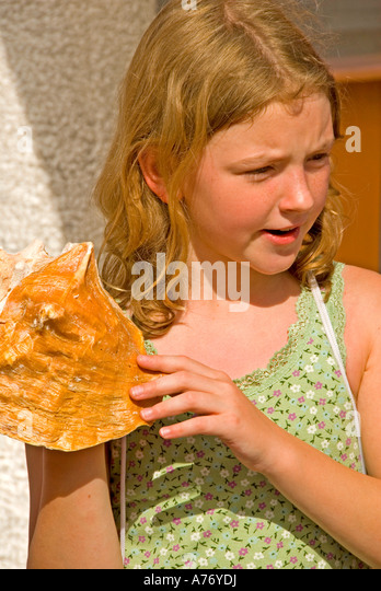 Cozumel Mexico San Miguel town girl learning to blow conch shell horn - Stock Image