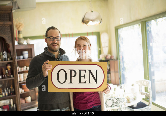 Two people standing in a store full of antique objects a couple running a business Holding a large sign saying OPEN - Stock Image