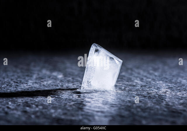 Melting ice cube in close up. Concept of cold temperature, water and change. - Stock Image