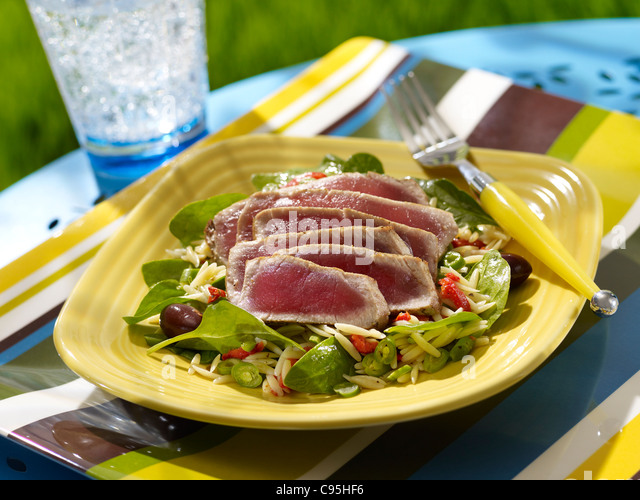 A seared ahi orzo salad with spinach and olives in an outdoor setting - Stock Image