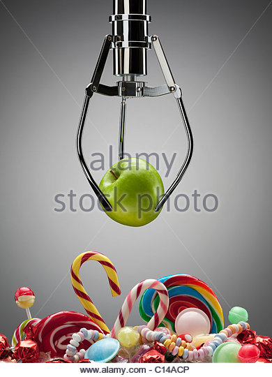 Hook with green apple above variety of sweet candies - Stock-Bilder