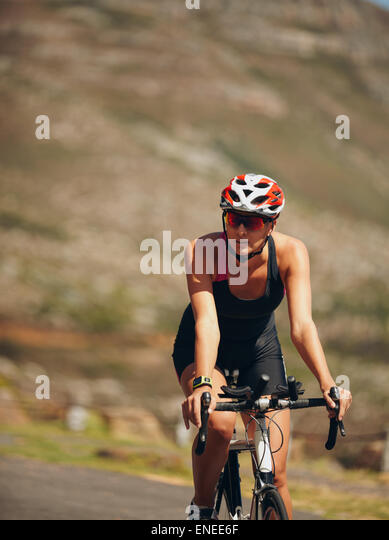 Shot of a female cyclist riding bicycle. Woman cycling on countryside road. - Stock Image