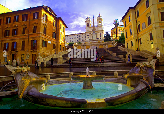 Rome, Italy; The fountain on Piazza di Spagna deigned by Bernini with the Church of Santa Trinita' dei Monte - Stock Image