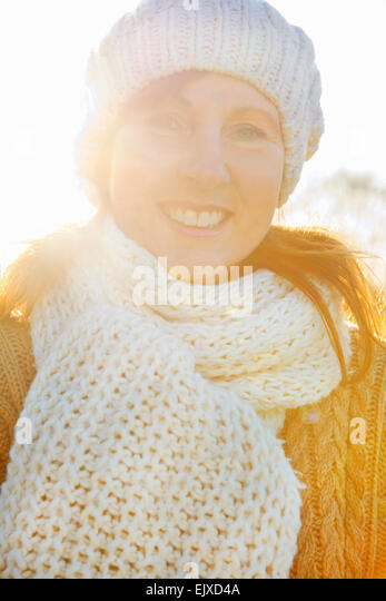 Woman Wearing Wool Hat and Scarf Smiling Outdoors - Stock Image