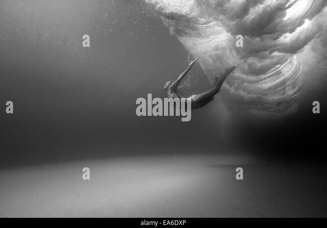 Woman swimming underwater - Stock Image