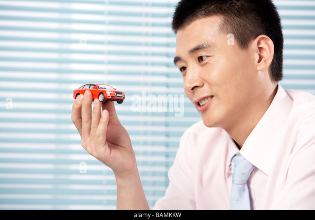 Businessman Holding A Red Toy Car - Stock Image