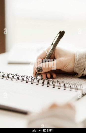 Cropped image of businesswoman writing in notebook at office desk - Stock Image