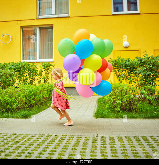happy little girl outdoors with balloons - Stock Image