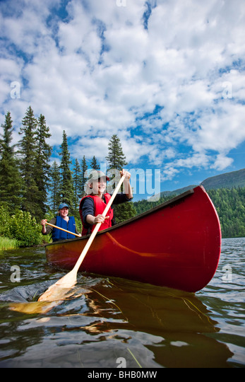 Mother and daughter paddling a canoe together on Byers Lake, Summer, Denali State Park, Southcentral Alaska, USA. - Stock Image