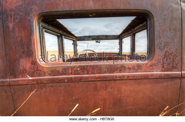 Rear view perspective of a vintage vehicle left to rot in a field. - Stock-Bilder