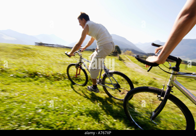 Young couple riding mountain bike, side view, (blurred motion) - Stock Image