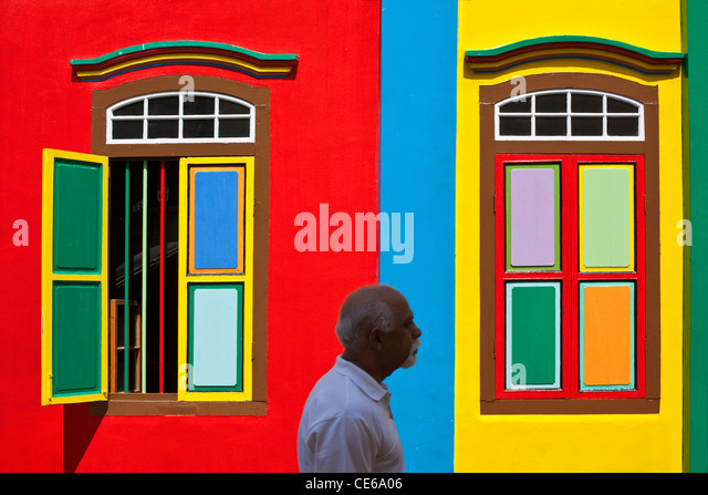 Man walking past a colouful heritage building in Little India, Singapore - Stock-Bilder