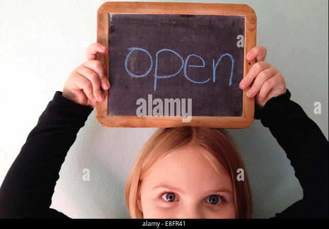 Portrait of a girl holding a blackboard above her head with the word open - Stock Image
