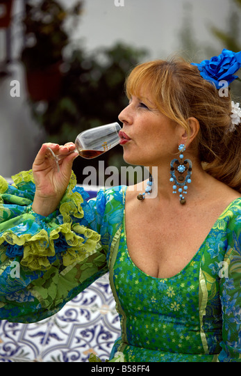 Spanish woman drinking glass of fino sherry, Fuengirola Feria, Andalucia, Costa del Sol, Spain, Europe - Stock Image