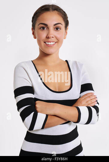 Stylish young woman in a striped top standing with her arms folded looking at the camera with a friendly smile - Stock Image