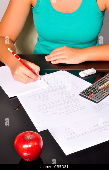 Student doing maths exercises with a calculator and a red pencil. - Stock Image